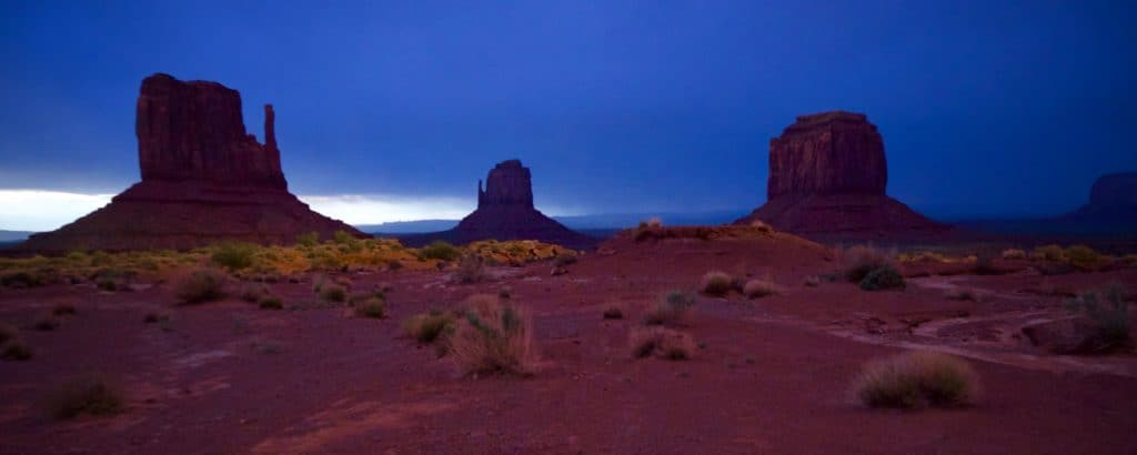 Night Photo. East and West Mittens and Merrick Butte at Monument Valley. Photography by Tim Bateman